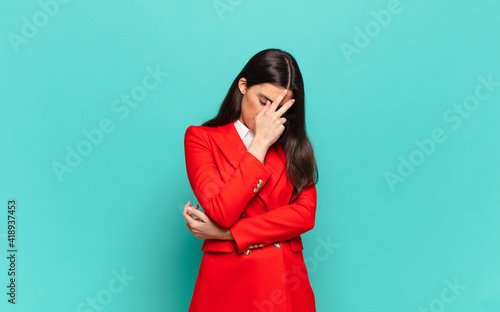 Tela young pretty woman looking stressed, ashamed or upset, with a headache, covering face with hand