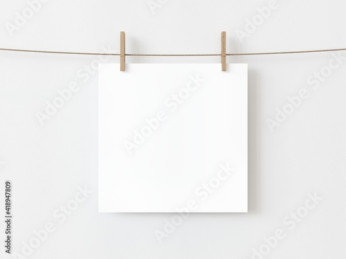 Photo One blank square note paper card hanging with wooden clip or clothespin on rope string peg isolated on white backgroun