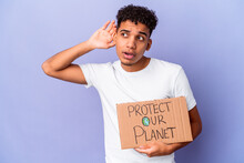Young African American Curly Man Isolated Holding A Protect Our Planet Trying To Listening A Gossip.