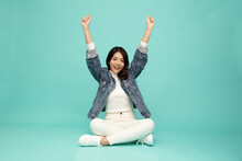 Attractive Beautiful Asian Woman Sitting On Floor And Hands Up Raised Arms From Happiness Isolated On Green Background, Excited Businesswoman Winner Success Concept