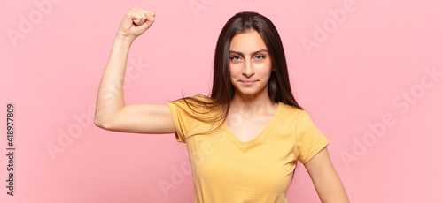 Fototapeta young pretty woman feeling serious, strong and rebellious, raising fist up, prot