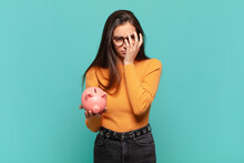 Young Pretty Woman Feeling Bored, Frustrated And Sleepy After A Tiresome, Dull And Tedious Task, Holding Face With Hand. Piggy Bank Concept