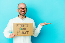 Young Caucasian Bald Man Holding A Protect Our Planet Placard Isolated On Purple Background Showing A Copy Space On A Palm And Holding Another Hand On Waist.