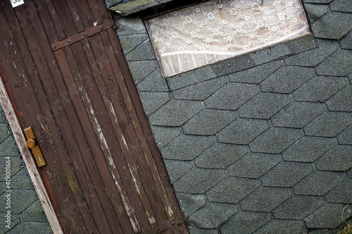 old wooden door and a window on a boathouse with tar paper Fotobehang
