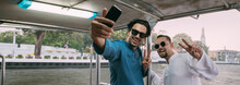 Young Men Sail On A Ship And Take A Selfie Against The Background Of A River In An Asian City