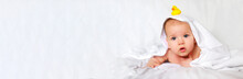 Banner Boy Dressed In A White Towel In A White Sunny Bedroom. Newborn Baby Is Resting In Bed After A Bath Or Shower. Textiles And Bedding For Children. Newborn Baby With Toy Yellow Ducks.