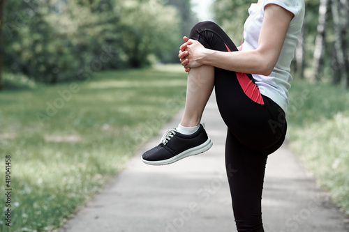 Obraz young fitness woman runner stretching legs before run on grass - fototapety do salonu