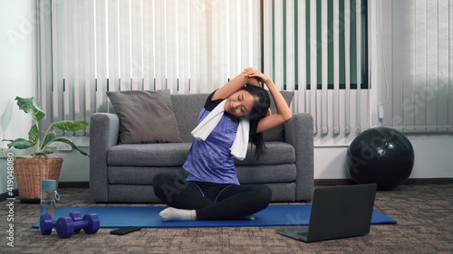 Obraz Asian woman stretching during a yoga class with a trainer at her laptop computer at home. - fototapety do salonu