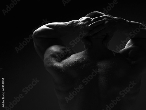 Fototapeta Strong muscular man, athlete, sportsman is standing naked, shirtless with his ba