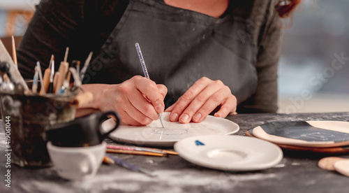 Obraz na plátne Woman drawing creative pattern on plate made at pottery workshop, top view