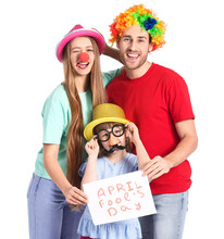 Young Family In Funny Disguise And With Poster On White Background. April Fools Day Celebration