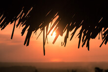 Silhouette Of A Sunset Behind Thatch Roof In Indonesia
