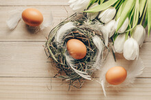 Egg Color. Happy Easter Decoration: Natural Colour Eggs In Basket With Spring Tulips, White Feathers On Wooden Table Background. Foil Minimalist Egg Design, Modern Top View Template.