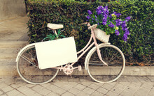 Pink Bicycle With Purple Flowers In A Basket And Blank Sign, Parked Next To A Park On The Street - Store Promotion
