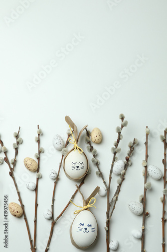 Easter eggs, quail eggs and catkins on white background