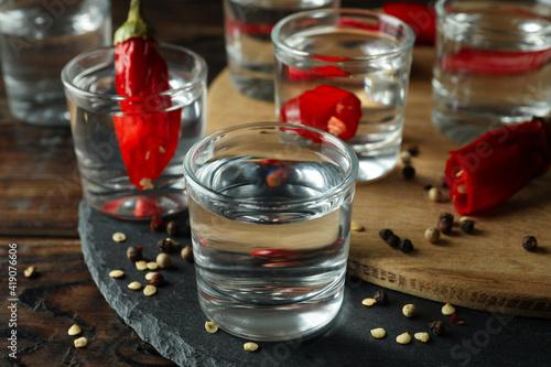 Fototapeta Shots of vodka and pepper on wooden background, close up obraz