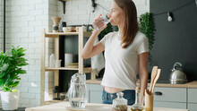Young Woman Pouring Water From Jug Into Glass In The Kitchen. Attractive Girl Drinking Water On Domestic Kitchen.