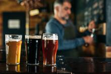 Middle Aged Man Bartender Serving Beer In Beer Pub