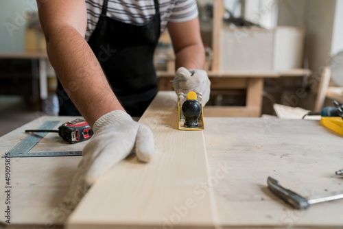 Carpenter working in his workshop, man planing and shaving a piece of wood Wallpaper Mural
