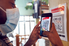 Man In Mask With Mobile Phone Checking Into Venue Scanning QR Code During Health Pandemic