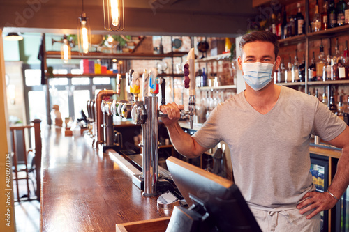 Fototapeta Portrait Of Male Bar Worker Wearing Face Mask During Health Pandemic Standing Behind Counter obraz