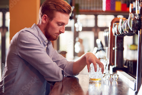 Fotografia Unhappy Man Sitting At Pub Bar Drinking Alone With Glass Of Whisky