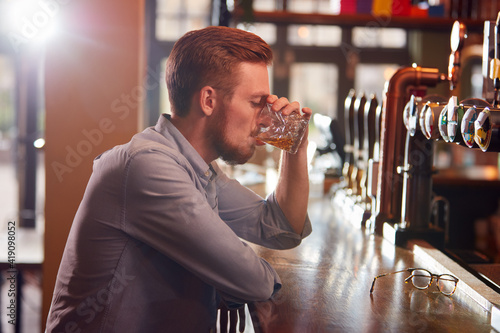 Canvas Print Unhappy Man Sitting At Pub Bar Drinking Alone With Glass Of Whisky