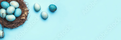 Obraz Easter eggs in nest on blue background. Flat lay, top view. - fototapety do salonu