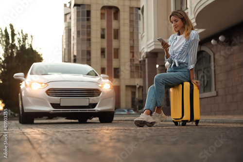 Photographie Woman ordering taxi with smartphone on city street