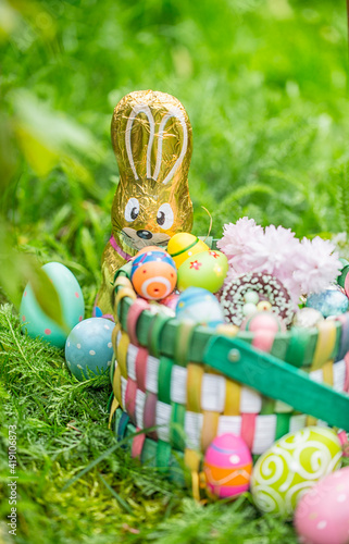 Wallpaper, Background, Postcard from easter greeting card with sweet snack basket, easter basket with sweets and chocolate eggs hidden in nature by the easter bunny.