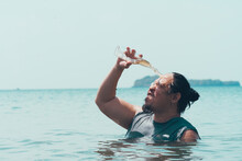 A Funny Asian Guy Pours A Bottle Of Beer On His Head While Standing Chest Deep In The Water At A Beach In The Middle Of The Day.