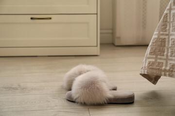 Grey fuzzy slippers on floor in room