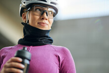 Portrait Of Cute Professional Female Cyclist Wearing Pink Suit And Neck Warmer Looking Away, Holding Water Bottle While Getting Ready For Training, Standing Outdoors On A Daytime