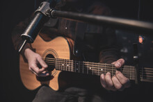 Close Up A Man Plays An Acoustic Guitar In A Dark Room.