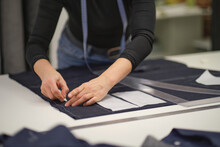 Seamstress Workplace. Woman Seamstress Makes Pattern With Chalk On Fabric For Sewing Clothes In Tailor Studio. Tailor Atelier Handmade Exclusive Clothes Making And Repair. Creative Occupation Concept