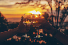 With Glasses Of Wine At Sunset. Selective Focus.
