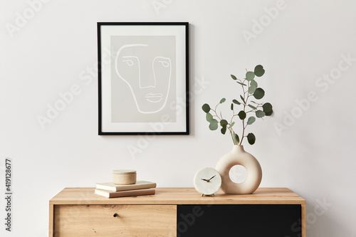 Stylish interior of living room with mock up poster frame, wooden commode, book, leaf in ceramic vase and elegant personal accessories. Minimalist concept of home decor. Template. - fototapety na wymiar