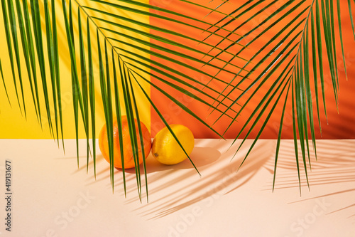 Fotografiet A fresh orange and a juicy lemon placed in a green palm leaf shade in front of vibrant yellow and orange background on sand color surface