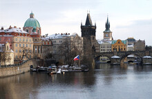 Touristic View Of Beautiful Snowing Prague, Vltava River, Charles Bridge And Prague Castle. The Red Roofs Of The Houses Are Covered With Snow.