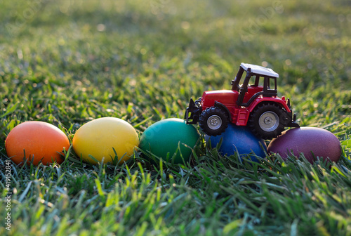 Fototapeta model of a toy red tractor, eggs painted in rainbow colors lie on the grass. Business concept of Easter greetings for farms. postcard. copy space obraz