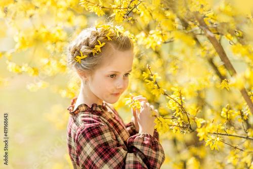 Fototapeta girl sniffs yellow flowers