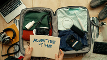 Man With Paper Notebook That Says Adventure Time Packs Suitcase For International Abroad Travel. Neatly Organized Personal Belongings. Top View Social Media Concept. Personal Items In Bag