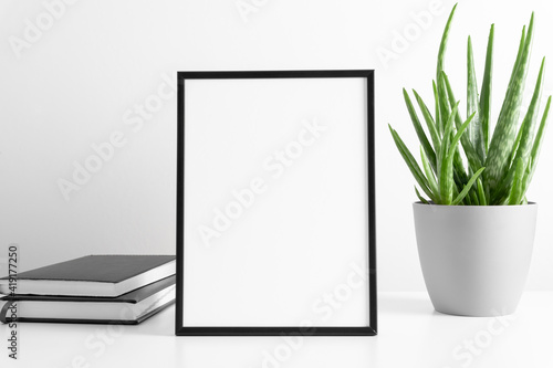 Obraz Black frame mockup with workspace accessories and aloe vera on white table. Front view. Place for text, copy space, mockup - fototapety do salonu