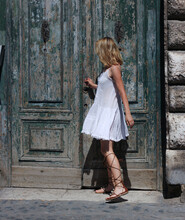 Beautiful Blonde, In A White Dress, Tries To Open An Old, Vintage, Green Door In Rome