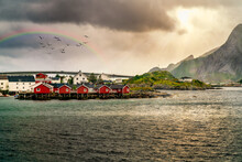 Classic Red Cabins In A Line In Lofoten, Norwat. Faded Rainbow Background With Flying Birds And A Setting Sun. Foreground Set With The Choppy Waters Of The Bay