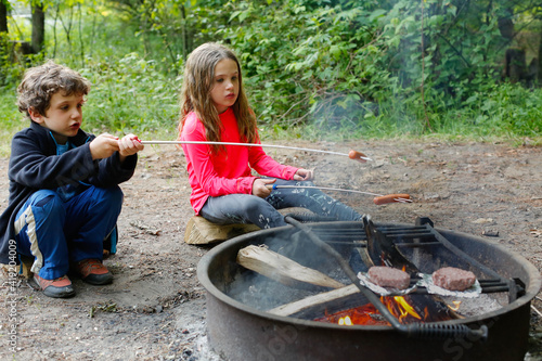 Two Children Roasting Hot Dogs while Camping