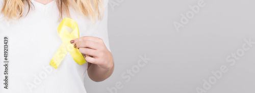 Fotografie, Tablou Young female in white t-shirt holding yellow ribbon awareness symbol for suicide, sarcoma bone cancer, bladder cancer, liver cancer and childhood cancer concept