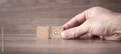 Obraz Man showing sad and happy smileys on wooden cube. Customer satisfaction - fototapety do salonu