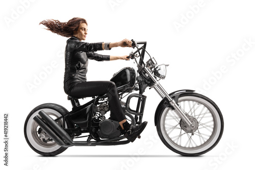Foto Full length profile shot of a woman with a long hair riding a custom chopper mot