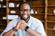 Headshot Of Friendly And Confident African-American Guy Wearing Stylish Eyeglasses And Smart Casual Wear, Looks At The Camera And Holds Hands In The Lock Near Chin. Employee Profile